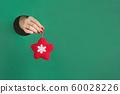 Female hand holding felt red star through hole 60028226