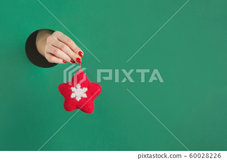 Female hand holding felt red star through hole 60028226