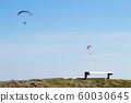 Paraglider on blue sky with empty bench on 60030645
