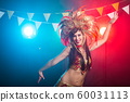 Carnival, belly dance and holiday concept - Beautiful female samba dancer wearing gold costume and smiling 60031113