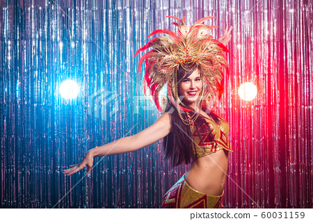 Carnival, belly dance and holiday concept - Beautiful female samba dancer wearing gold costume and smiling 60031159
