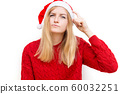 Thinking and reflecting girl in a Christmas hat. emotional woman in red santa claus hat. Holiday concept. Emotion facial expression. 60032251