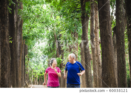 happy asian senior couple jogging together at 60038121