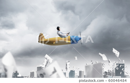 Businessman in aviator hat driving paper plane 60046484
