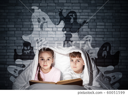 Cute girl and boy reading book in bed 60051599