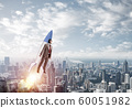 Business person in aviator hat flying on rocket 60051982