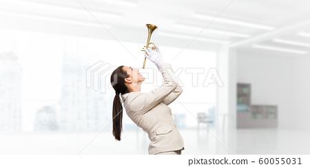 Beautiful woman holding trumpet brass overhead 60055031