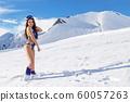 Woman wearing bikini standing on snow mountain top in ski resort. Beautiful mountains view background. 60057263