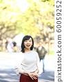 漫步在外灘前的銀杏樹上的年輕女子 60059252