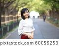 漫步在外灘前的銀杏樹上的年輕女子 60059253