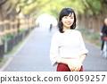 漫步在外灘前的銀杏樹上的年輕女子 60059257