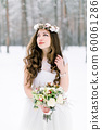 Winter wedding portrait. Portrait of beautiful bride with floral and cotton wreath on the head, holding bouquet, wearing a white dress against the background of the winter forest in snowy weather 60061286