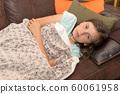 sick teenage girl lying on the sofa 60061958