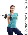 Beautiful fit girl lifting a dumbbell 60062043