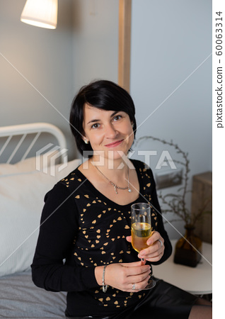 Beautiful woman 50 years old in bed with a glass 60063314