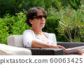Portrait of  smiling middle age woman sitting in 60063425