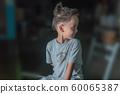 a cute boy sitting in the dark 60065387