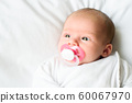 Newborn Baby Portrait, Beautiful New Born Kid sucking Pacifier, Child four weeks old. Copy space on left. 60067970