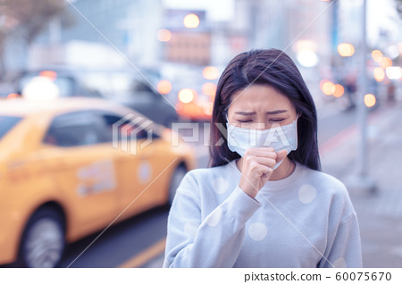 young  woman wear mask in the city during Smog day 60075670