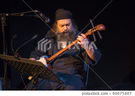 Man in black sits and plays shamisen  60075807