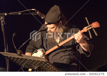 Man in black sits and plays shamisen  60082279