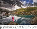 Hiking woman in red jacket stay at beautiful reflection of a lake in mountains. 60085120