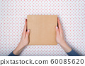 Square cardboard box in female hands. Top view, 60085620
