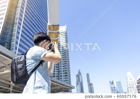 Young traveler looking at viewfinder of camera 60087576