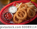 french fries and onion rings in plastic basket 60089114