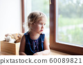 Sad child is sitting on window sill. Cute kid is looking through window. Little girl is worry, bored 60089821