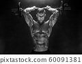 Strong sportsman lifting heavy dumbbell in smoke 60091381