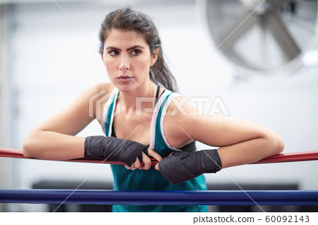 A badass female boxer is resting on ring ropes 60092143