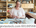 Woman working on a gemstone necklace as a hobby 60100568