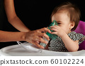 Little baby girl with breathing mask 60102224