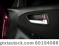 Car door lock / unlock button and metallic handle on the car door panel. 60104088