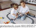 Children playing with lego and toy train in a playing room 60105657