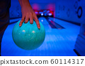 Men's hand holding a blue bowling ball ready to 60114317