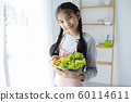 Asian girl wearing apron, smiling and holding vegetable basket in kitchen 60114611