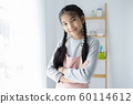 Young Asian girl wearing apron, smiling and crossing arms in kitchen. 60114612