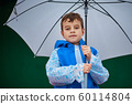 Close up portrait of boy in blue raincoat hold umbrella in rainy day 60114804