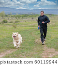 Young man running with your golden retriever dog 60119944