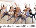 Group of young sporty attractive people in yoga studio, practicing yoga lesson with instructor, stretching on floor in Trikonosana, triangle yoga pose. Healthy active lifestyle, working out in gym. 60120806