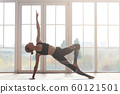 Young lady demonstrating beautiful strong body at yoga studio 60121501
