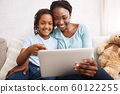 Afro mom and daughter making video call 60122255