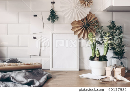 Christmas still life. Blank wooden picture frame and greeting cards mockup with paper stars, eucalyptus, potted hyacinth flowers and gift wrapping papers. White tiles background. Winter composition. 60137982