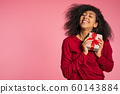 Beautiful african american woman received gift box with bow. She is happy and flattered by attention. Girl on studio background. 60143884