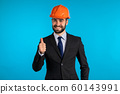 Positive young engineer businessman in construction helmet smiles to camera. Man showing thumbs up sign over blue background. Winner. Success. Body language. 60143991