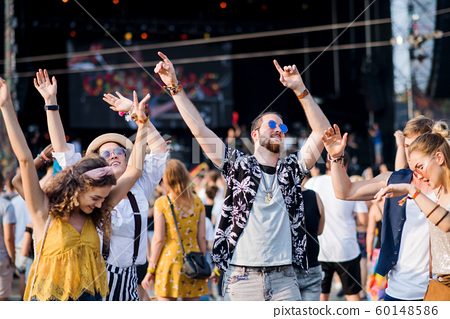Front view portrait of group of young friends dancing at summer festival. 60148586