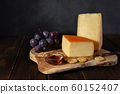 Cheese on a wooden board with nuts and honey 60152407