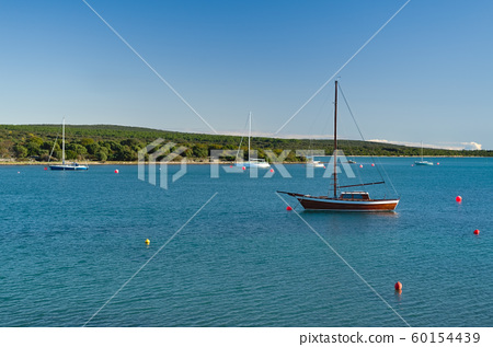 Some sailboats moored in a cove on the Croatian coast near the port of the Osor village, Losinj island 60154439